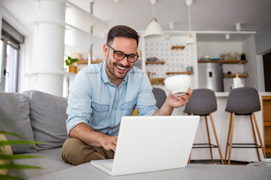 Young attractive man sitting on sofa at home working on laptop online, using internet, smiling, happy mood, freelancer, free leisure time, relaxed, modern job lifestyle