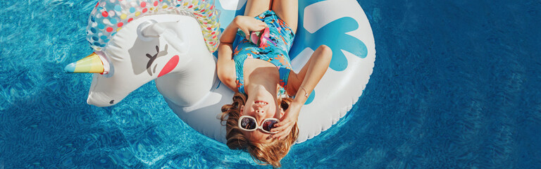 Fototapeta Cute adorable girl in sunglasses with drink lying on inflatable ring unicorn. Kid child enjoying having fun in swimming pool. Summer outdoors water activity for kids. Web banner header.