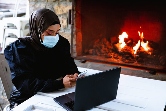Professional Muslim businesswoman working remote at local coffee shop