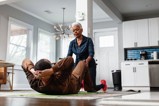 Senior wife helps train husband and exercise in living room
