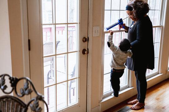 Black grandmother woman weather sealing, caulking windows for winter with toddler grandson