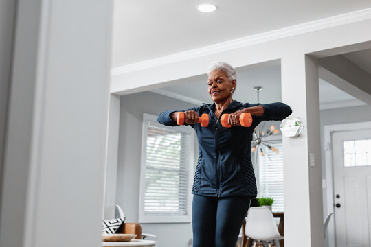 Senior Black woman exercising at home, active lifestyle fitness