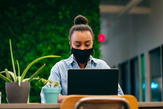Woman wearing a mask working safely in office space