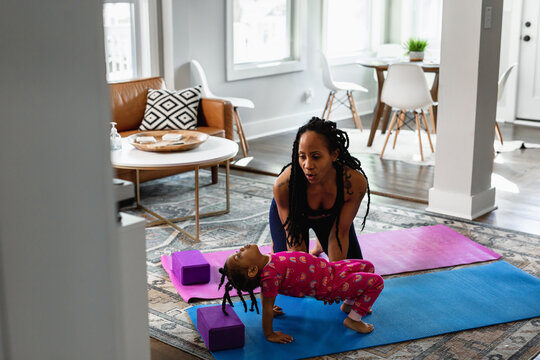 African American mother helping daughter exercise
