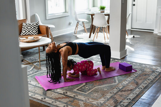 Black mother does yoga pose with daughter toddler