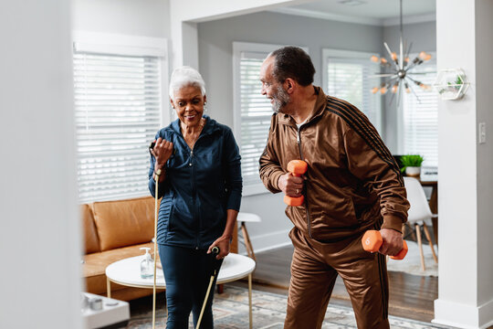 African American senior couple exercises together at home