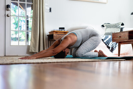 Black woman does downward dog pose in yoga mat