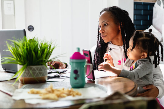 Woman working from home with child toddler