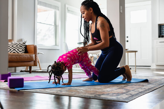 African American mother helping daughter exercise at home