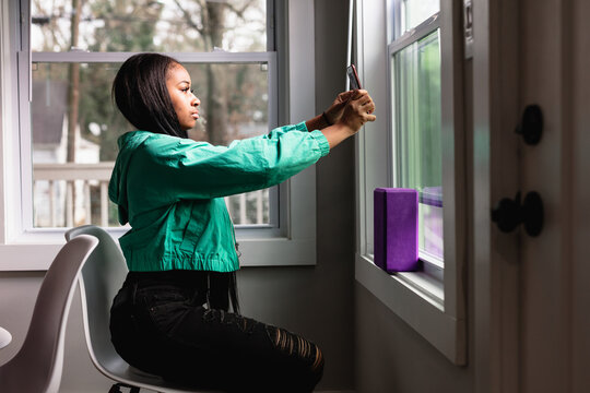 Teen girl taking selfie by window for best light and angle