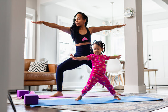 Black Mother and daughter doing yoga in family room, warrior pose