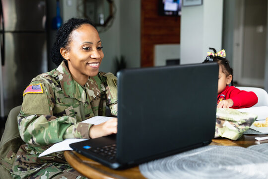 Happy military woman has conversation with family while working from home at laptop