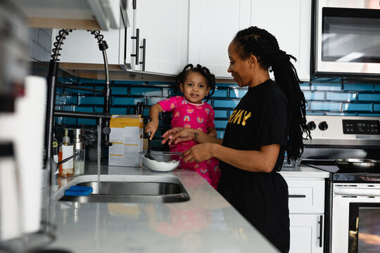Military mother prepares breakfast with daughter