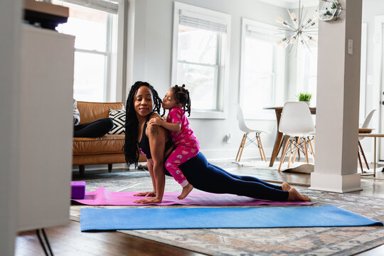 Mother and daughter working out at home doing exercises