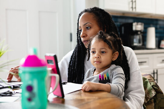 Black woman working from home with toddler child sitting on lap
