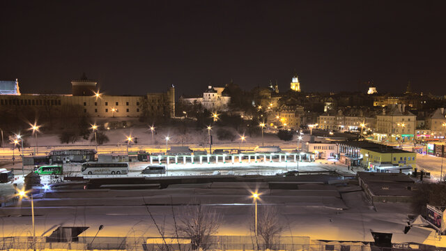 Snow-covered bus station against the backdrop of the night city