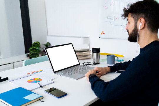 Young businessman looking at laptop in creative office