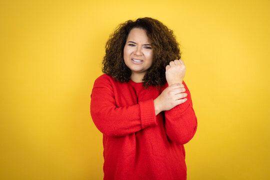 Young african american woman wearing red sweater over yellow background suffering pain on hands and fingers, arthritis inflammation