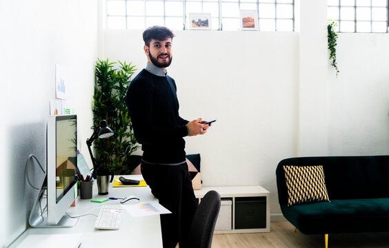 Portrait of businessman with smart phone standing at desk in office