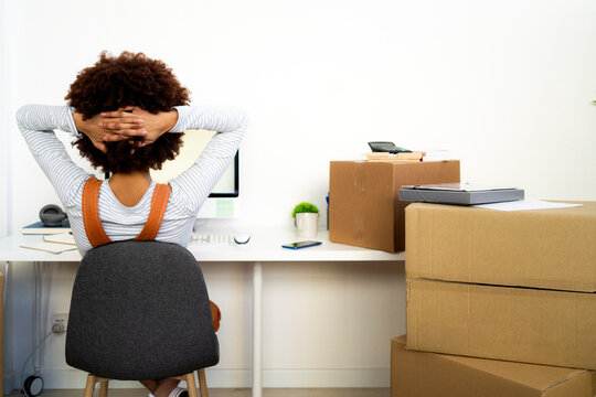 Afro woman with hand behind head relaxing by cardboard boxes in new home