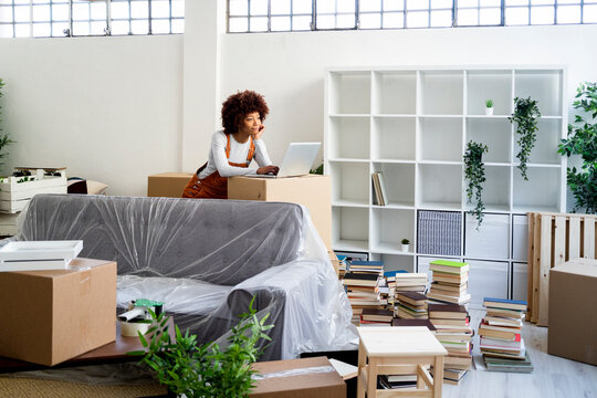 Afro woman with laptop leaning on cardboard box while moving into new home