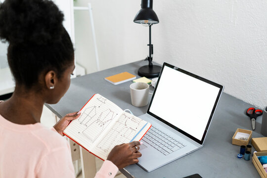 Fashion stylist with laptop analyzing diagram in book while sitting at home