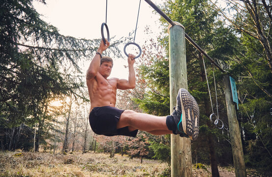 Shirtless male athlete hanging on gymnastic rings on fitness trail in forest