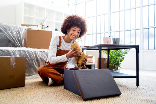 Smiling Afro woman keeping wrapped glasses in box while moving into new house