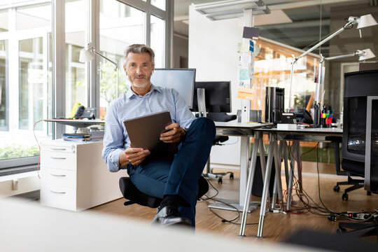 Confident entrepreneur with digital tablet sitting at open plan office