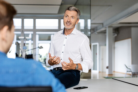Mature businessman discussing with colleague while sitting at office