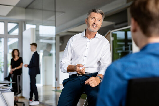 Business people having discussion while sitting with colleague in background at open plan office