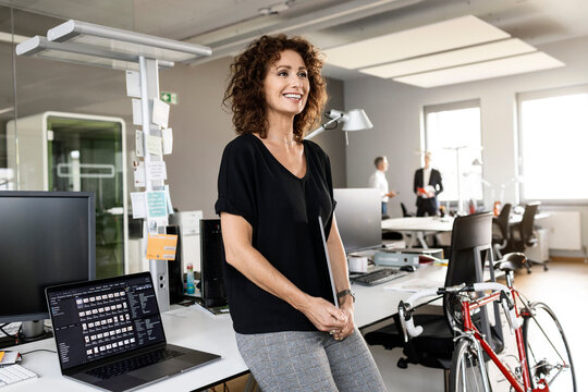 Smiling entrepreneur with digital tablet looking away while standing at open plan office