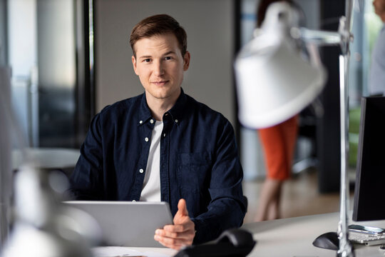 Confident young businessman using digital tablet while sitting at office