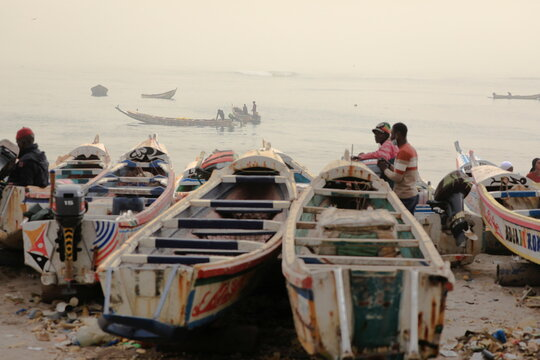 Fishermen are pictured on their pirogue as dust carried by winds from the Sahara Desert shrouds Dakar,