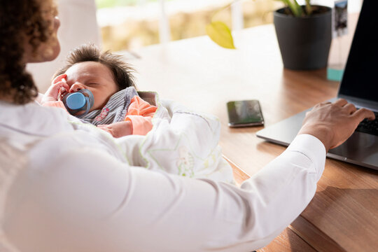 Mother holding sleeping baby while working on laptop at home