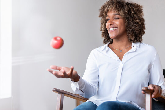 Woman smiling while playing with apple sitting on armchair at home