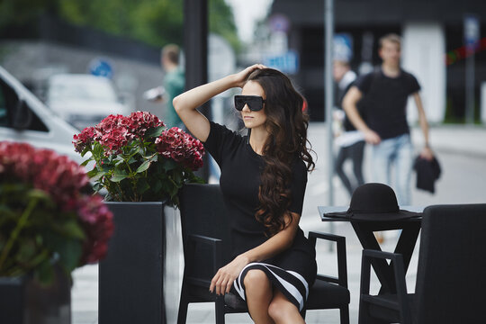 Outdoor summer portrait of a young woman wearing trendy sunglasses and fashionable dress sitting at the cafe table in the street of a European city