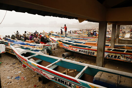People are pictured at the fishing port of Soumbedioune as dust carried by winds from the Sahara Desert shrouds Dakar