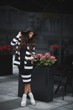 Adult woman in a modish black hat and fashionable white shoes posing on the European city street