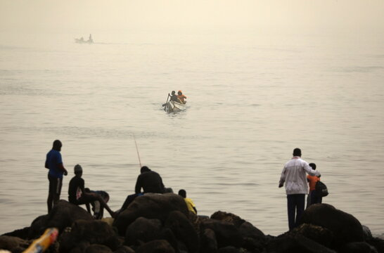 Fishermen are pictured on their pirogue as dust carried by winds from the Sahara Desert shrouds Dakar