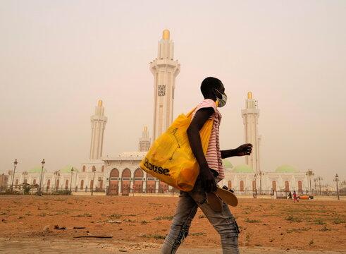 A street vendor walks past the Massalikoul Djinane mosque as dust carried by winds from the Sahara desert shrouds Dakar