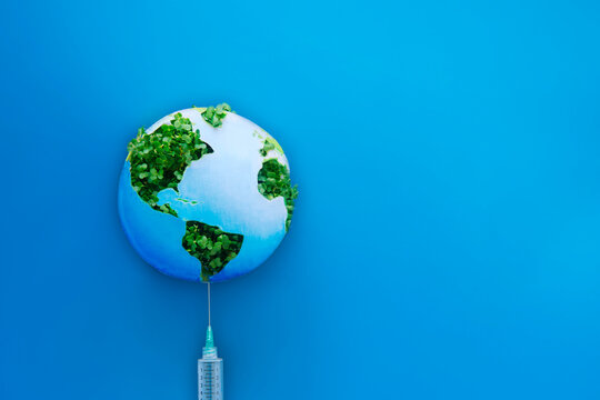 Creative Global Vaccination Concept. Planet Earth model made of paper and fresh green sprouts on the needle of the syringe on blue background. Covid vaccine. Selective focus, copy space for text.