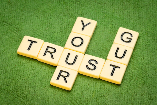 trust your gut crossword in letter tiles against textured handmade paper, advice or motivational reminder and personal development concept