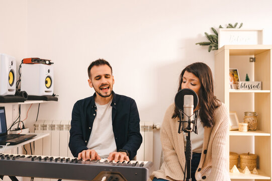 Male musician playing synthesizer and singing together with woman while recording song at home