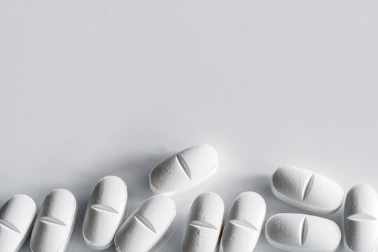 Top view of assorted white pills placed on white table
