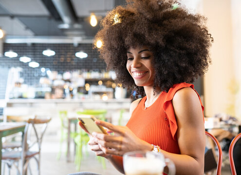 Side view of smiling African American female with curly hair sitting in cafe and messaging on social media via mobile phone