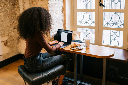 Woman with curly hair working with a laptop in a coffee shop
