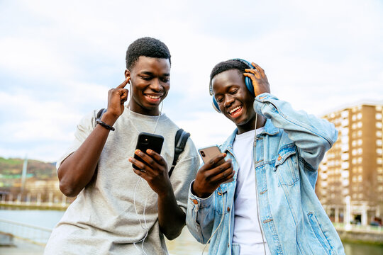 Young content ethnic partners with cellphones listening to song from earphones and headset on urban embankment under cloudy sky