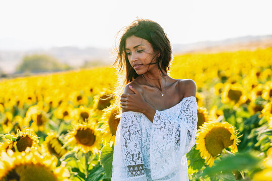 Thoughtful ethnic female standing in booming sunflower field and looking away