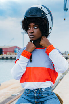 Concentrated young black female biker with Afro hair in trendy outfit and helmet while sitting on motorcycle at seaside